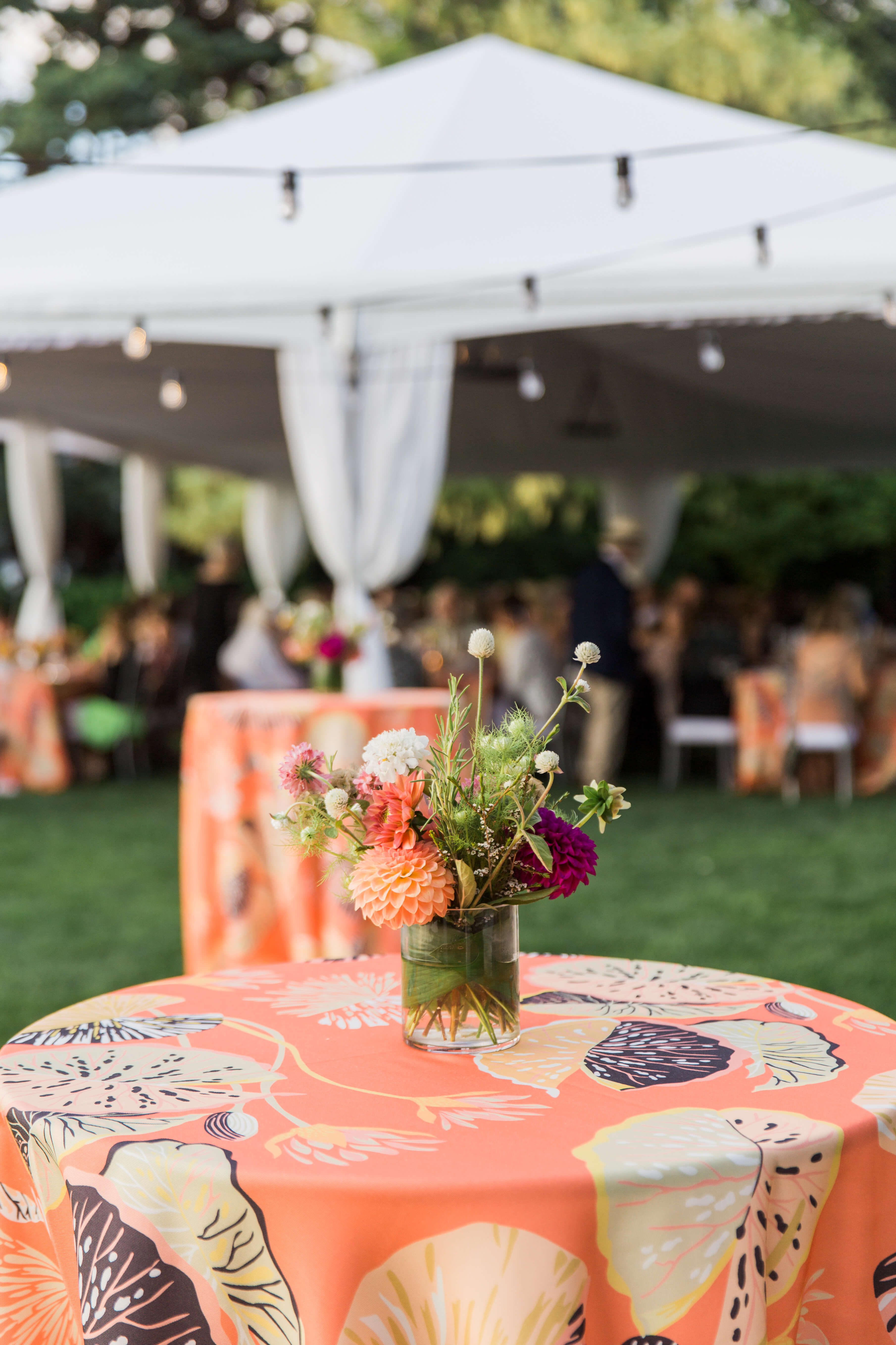hi boy tables on the lawn adorned with small florals