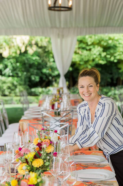 jean louise placing centerpieces on a long king's table